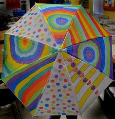 students paint plain white umbrellas for a school fundraiser cute idea but would be fun just for a spring craft project