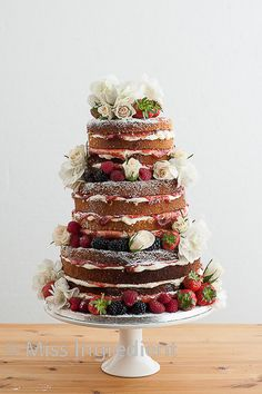 naked wedding cake with stacked with strawberries and blackberries and pretty fresh flowers