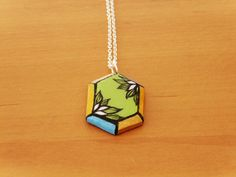 The cartoon style makes the colours pop! This is a whimsical looking necklace for those with bit of whimsy.Pendant handmade from polymer clay, painted with acrylic, and coated with resin. Silver plated chain.