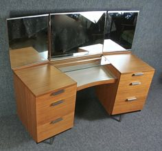 The stag Fineline range was designed by John and Sylvia Reid in 1959 and retailed from 1960-63. It featured innovative finishes… 'pin-stripe' birch veneers, and satin stainless steel handles and legs. The design has a wrap around shape with adjustable mirrors and a practical white laminated top with a glass shelf to display cosmetics and …