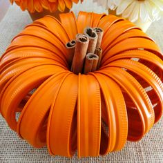 Mason Jar Lid Pumpkins with Cinnamon Stick stem makes the cutest fall centerpiece. It is easy to make and you only need lids and spray paint!