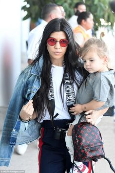 Flying mate: Kourtney also flew out with the group and carried son Reign on her hip