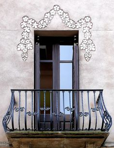 Art Nouveau in delicate floral garland above French doorway and an iron bombe balcony, Barcelona (SP)
