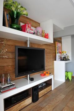 O aspecto rústico da madeira presente no piso e na parede é quebrado por elementos como a estante de laca branca, desenhada por Guto Requena. Como uma fita, a estante que se dobra percorrendo toda a sala, ora junto ao teto, ora ao piso