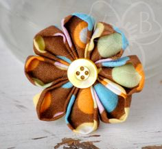 """""""Falling Spots"""" is a speckled daisy style kanzashi flower in fun fall colors, with a yellow button center.  """"Falling Spots"""" is secured to an alligator clip for wear in your hair, clipped to your lapel, headband, purse or more."""