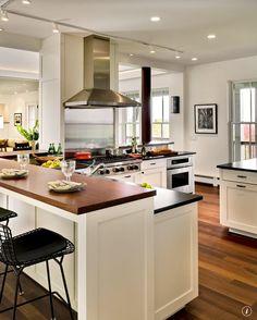 Wooden bar top, stainless steel hood and stove, hardwood floors, open concept kiTchen- LJKoike