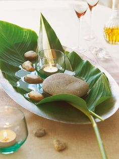 Blatt mit Wasser, Steinen und Kerze.
