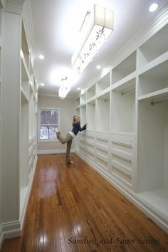 Walk in master closet with white built in cabinets