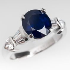 This stunning Verragio ring is set with a 3.1 carat natural blue sapphire and is crafted of 18k white gold. The sapphire is a dark rich color and is lovely. The ring is accented with pear brilliant cut and tapered baguette cut diamonds and is in excellent condition. It currently fits like a size 6.5 with two small sizer nubs installed to help keep the ring from spinning on the finger. The ring can be re-sized prior to shipping and we offer this service complimentary.