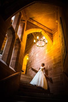 Bride on staircase at Peckforton Castle wedding venue in Cheshire, Chester, North West