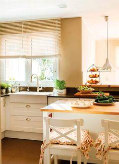 Cocina con isla con barra de desayunos, cajones, persianas venecianas y taburetes con cojines de asiento de flores