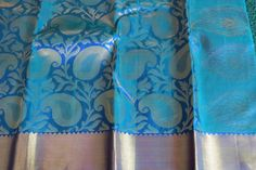 This peacock blue saree is stunning in pure silk direct from the weavers of Kanjivaram, the weavers' town in TamilNadu. Some of the highest quality pure silk is found in this saree that has jaquard paisley motifs all over with a thick gold border The pallu is ravishing with all over Zari and border. The blouse is in double shade blue to give a special effect: the gold zari border is repeated in the blouse. This Zari is Fine zari.