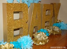 Image from http://www.handcraftedparties.com/wp-content/uploads/2014/01/Boy-baby-shower-decor_glittered-letters-and-tissue-poms_Handcrafted-Parties.jpg.