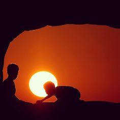 El sol se pone, mientras pequeños palestinos juegan en una cueva a la orilla de una playa en Gaza.  Foto: AFP