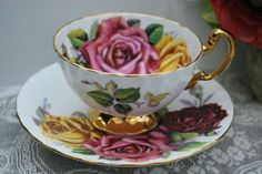 Pink and yellow tea cup with blue and pink flowers | Aynsley Tea Cup and Saucer Large Roses