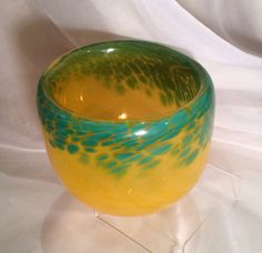 This gorgeous glass art bowl adds a dash of Spring to your decor! The hand blown glass bowl is a semi translucent shade of orangey-yellow with green