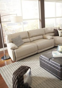 Make an impact on your room with the Auburn Hills sectional. Upholstered in supple leather wherever the body touches, the sectional features a neutral taupe color, generous seating and four recliners with padded chaise footrests.