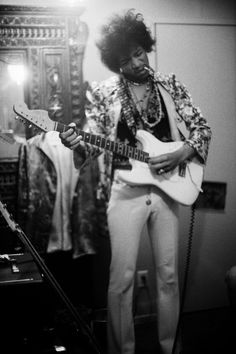 Jimi Hendrix played his guitar in the dressing room before the Jimi Hendrix Experience performed at the Hollywood Bowl, 1967.