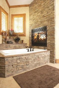 Stone Wall Bathroom with Drop In Bathtub containing: Bronze Finished Tub Faucet with Built In Fireplace also Dark Metal Fireplace Frame plus Classic Style Candle Holder together with Gray Bathroom Rug