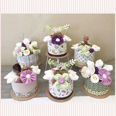 """This listing is for SIX mid-sized elegant mini diaper cake centerpieces decorated in a sweet gender neutral woodland theme. Each cake has an assortment of diaper lilies, washcloth roses and flowers arranged on an 8"""" diaper cake base. (Larger quantities and/or coordinating"""