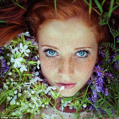 Another young woman looks up into the camera from a bed of purple wildflowers, which offset the bright tone of her hair