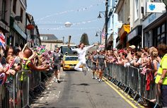 Nadine Struijk of The Netherlands, carrying the Olympic flame during the torch relay through Brynmawr, Wales, on May 25. Struijk was in the Dutch national synchronized swimming team for many years and now coaches the junior Dutch team, but gets her moment to shine here in the torch relay running up to the London Olympic Games. (Gareth Fuller/Locog via Associated Press)