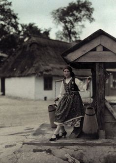 A peasant girl balances water pails with a wooden yoke by a well.  Location:Bronowice, Poland.  Photographer:HANS HILDENBRAND/National Geographic Stock