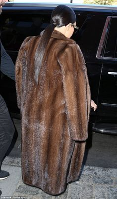 She's got it covered: She wore a huge fur coat for the outing, despite the sunny weather ...