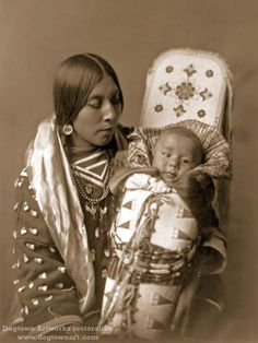 Crow Mother and Child is a restored reprint of a vintage photograph taken by the great photographer, Edward Curtis. Crow Mother and Child features a mother holding her child on a cradle board. They are members of the Crow Tribe. The photo was taken in the early 1900s. This is an 8.25 X 11-inch