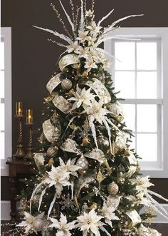 An absolutely stunning Christmas tree with white poinsettia and beautifully garland wire edge ribbon through this tree. Elegantly illuminated with warm white lighting.