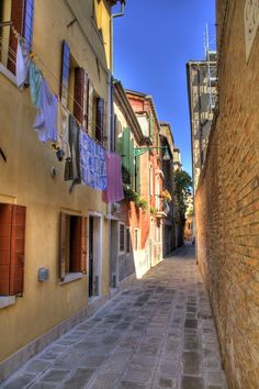 This is a little alley in the sestiere Cannaregio in Venice, Italy. The clothes drying over the alley are really representative of those mediterranean countries.!