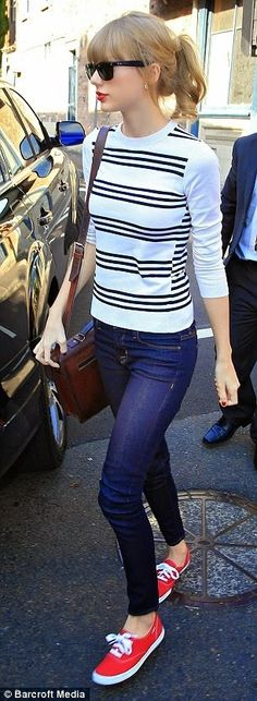 #TaylorSwift looks adorable in a black and white striped sweater, skinnies, and red tennis shoes