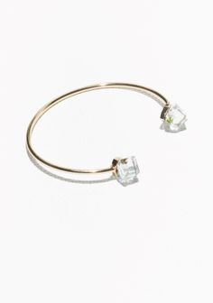 Modern rectangular shape and glistening glass stones define this swanky cuff made of brass.