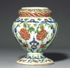 AN IZNIK POTTERY FLOWER-VASE  OTTOMAN TURKEY, CIRCA 1590  Of baluster form with raised and inverted mouth on spreading foot, the shoulder pierced with a band of holes for the stems of flowers, the white ground of the body painted in cobalt-blue, bole-red and green with small arabesques flanked by scrolling paired peonies and divided by paired cypress trees, a band of lappets around the shoulder and foot, the mouth with interlaced rope pattern on red ground,   6½in. (16.5cm.) high