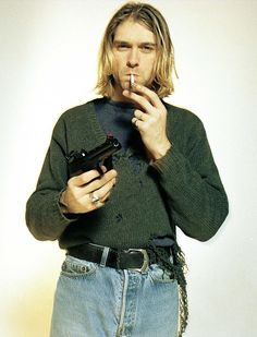 Kurt Cobain poses with a gun in a tattered knit sweater with high waist light wash denim jeans.