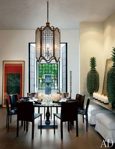 A massive bronze-and-beveled-glass light fixture presides over the dining area of Michael Schaible's exotic yet minimalist home on the banks of Mexico's Lake Chapala. | archdigest.com