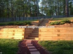 Pressure treated lumber retaining wall with steps and walkway. Retaining wall is tiered Lilburn, Ga Cheap Retaining Wall, Retaining Wall Steps, Backyard Retaining Walls, Railroad Tie Retaining Wall, Sleeper Retaining Wall, Retaining Wall Design, Sloped Backyard Landscaping, Sloped Yard, Back Gardens