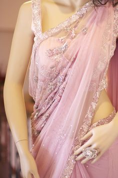 Lavender pre-pleated net saree. Pearl embellished broach on pleats. Cascading embroidery in sequins, beads and thread work on pallu part. Silver and pink sequins on entire border. Scattered star bust