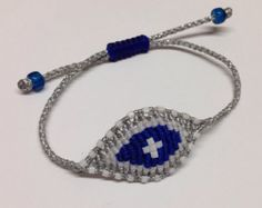 This is a handmade macrame bracelet with waxed cord and white beads. The eye of this hand-knotted macrame bracelet measures approximately