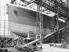 As this photograph shows, a grandstand for spectators was erected beneath Titanic's towering bow, in preparation for the launch.    Horses can be seen standing patiently in the shafts of their carts.   High on the deck a few shipyard workers look down from the great ship they have helped to build.   The name 'Titanic' has been enhanced by the photographer on his glass plate negative.