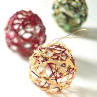 Ball-of-String Christmas Ornament:   These delicate-looking ornaments are made from basic crafts supplies: glue, string, and glitter. Use string in Christmas colors for extra cheer. What You'll Need: Small water balloons,   White glue,   Water,   Small bowl,   Desired colors of narrow cording or yarn cut to 10-inch lengths,   Waxed paper,   Iridescent glitter. How to Make It:   1. Blow up balloons to make small round shapes; tie ends.   2. In a small bowl make a solution of 2 parts glue and…