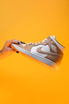 """Ready to take the Air Jordan 1 Mid for a spin? A shoe that's only gained in popularity over the years, the mid-top version of Michael Jordan's first signature shoe is a great entry point to the Air Jordan collection, especially in this """"Tan/Gum"""" style."""