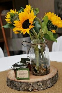 Sunflower in a mason jar with twine wrapped into a bow, on top a simple wooden base.