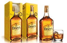 Drury's lança pack especial com copo de uísque  A embalagem reforça as cores e o brasão da marca. A foto da garrafa em tamanho real na embalagem permite que o design se integre de maneira natural ao produto. O design é da agência eba!.
