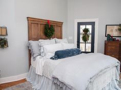 A custom wood headboard and antique dresser pair nicely with the new wood flooring. A door in this bedroom offers access to a side porch.