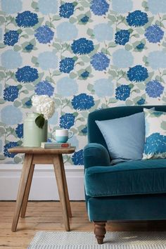 A pretty stylised digitally printed Lorna Syson wallpaper design - with bold blue hydrangea flowers, sprinkled with tiny red ladybirds.