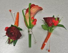 Boutonnieres - mango cala lily, deep red spray roses and berries