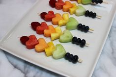 Fresh fruit heart skewers using watermelon,cantaloupe, honeydew, pineapple, blueberries and raspberries. A fun and colorful snack you can make with your kid as a Valentine's Day treat or really any time of year!
