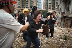 A woman who tries to protect her house being demolished is stopped by Chinese staff at Yangji village in Guangzhou city, south Chinas Guangdong province, 21 March 2012. The second-phase demolition of Yangji village Wednesday (21 March 2012) began in Guangzhou city, south Chinas Guangdong province.