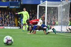 Chelsea's Belgian goalkeeper Thibaut Courtois gestures as Manchester United's Ivorian defender Eric Bailly and Chelsea's English defender Gary Cahill...